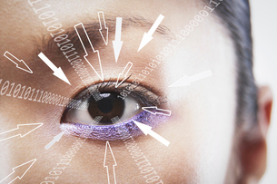 Close-up portrait of businesswoman with binary digits and arrow signs moving towards his eyeの写真素材 [FYI03651779]