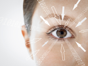 Close-up portrait of businesswoman with binary digits and arrow signs moving towards her eye againstの写真素材 [FYI03651782]