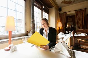Beautiful customer reading menu at restaurant tableの写真素材 [FYI03651808]