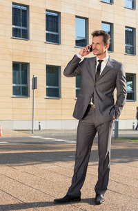 Full length of businessman conversing on cell phone against office buildingの写真素材 [FYI03651847]