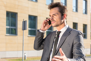 Young businessman conversing on cell phone against office buildingの写真素材 [FYI03651851]