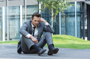 Full length of depressed businessman sitting on path outside officeの写真素材 [FYI03651852]