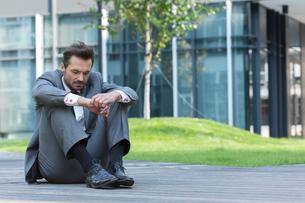 Full length of sad businessman sitting on path outside officeの写真素材 [FYI03651853]