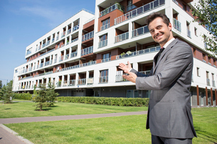 Portrait of smiling real estate agent presenting office buildingの写真素材 [FYI03651855]