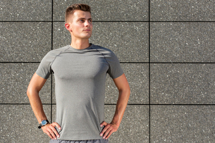 Determined jogger standing against tiled wall outdoorsの写真素材 [FYI03651861]