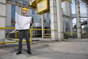 Full length of young male architect with blueprint outside industryの写真素材 [FYI03651865]