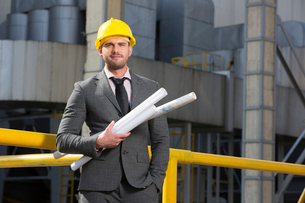 Portrait of confident young businessman holding blueprints outside industryの写真素材 [FYI03651866]