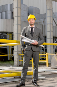 Portrait of confident young businessman holding rolled up blueprints outside industryの写真素材 [FYI03651868]
