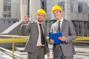 Young male engineers with clipboard discussing outside industryの写真素材 [FYI03651871]