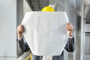 Young male architect analyzing blueprint in industryの写真素材 [FYI03651876]