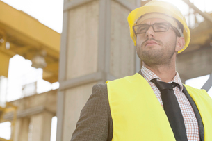 Thoughtful young male architect in protective wear at construction siteの写真素材 [FYI03651883]