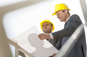 Low angle view of young businessmen holding blueprint against clear skyの写真素材 [FYI03651886]