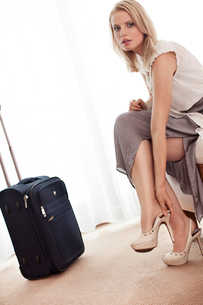 Full length portrait of young businesswoman taking off her shoes in hotel roomの写真素材 [FYI03651890]