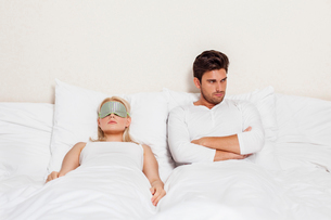 Angry young man with woman sleeping in bedの写真素材 [FYI03651891]