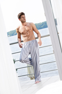 Full length of handsome young man leaning on hotel balcony looking awayの写真素材 [FYI03651910]