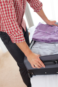 Midsection of young man unpacking suitcase in hotel roomの写真素材 [FYI03651911]