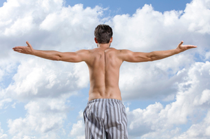Rear view of shirtless young man standing arms outstretched against cloudy skyの写真素材 [FYI03651915]