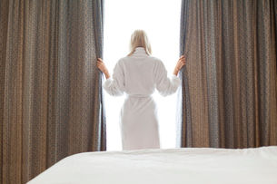 Rear view of young woman in bathrobe opening window curtains at hotel roomの写真素材 [FYI03651917]