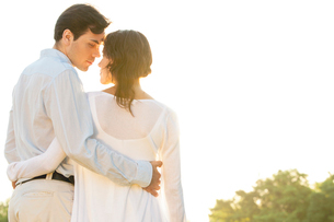 Rear view of romantic couple standing arms around against clear skyの写真素材 [FYI03651922]
