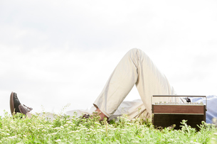 Low section of man lying by vintage radio on grass against clear skyの写真素材 [FYI03651938]