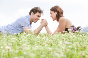 Side view of young couple arm wrestling while lying on grass against skyの写真素材 [FYI03651944]