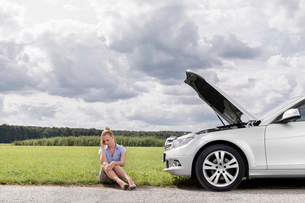 Full length of sad businesswoman sitting by broken down car at countrysideの写真素材 [FYI03651954]