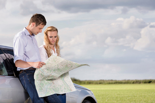 Couple reading map while leaning on car at countrysideの写真素材 [FYI03651959]