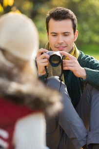 Young man photographing woman in parkの写真素材 [FYI03651976]