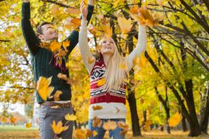 Couple enjoying falling autumn leaves in parkの写真素材 [FYI03651979]