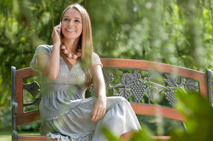 Beautiful young woman using cell phone on bench in parkの写真素材 [FYI03652027]