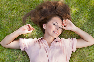 High angle portrait of beautiful young woman lying in grassの写真素材 [FYI03652040]