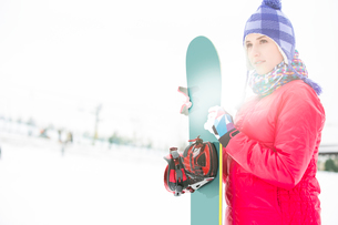 Beautiful young woman in warm clothing holding snowboard during winterの写真素材 [FYI03652054]