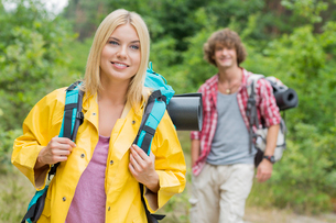 Smiling female backpacker looking away with man standing in background at forestの写真素材 [FYI03652072]