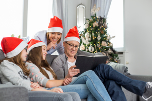 Family of four reading book in living room during Christmasの写真素材 [FYI03652094]