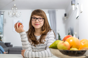 Portrait of teenage girl holding apple at homeの写真素材 [FYI03652100]