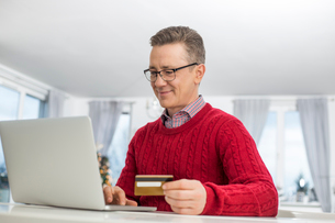 Mature man using credit card and laptop to shop online during Christmasの写真素材 [FYI03652101]