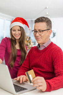 Smiling father and daughter shopping online at home during Christmasの写真素材 [FYI03652102]
