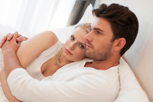 Loving young couple embracing in bedの写真素材 [FYI03652124]