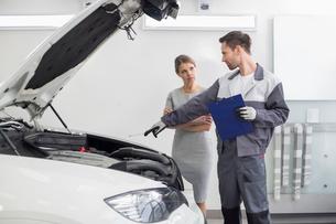 Young male repairman explaining car engine to female customer in automobile repair shopの写真素材 [FYI03652131]