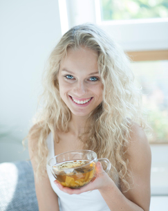 Portrait of happy young woman holding herbal tea cup in houseの写真素材 [FYI03652152]