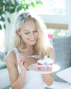 Beautiful woman having raspberry cake with fork in houseの写真素材 [FYI03652154]