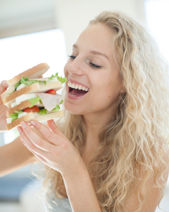 Happy woman eating large sandwich in houseの写真素材 [FYI03652182]