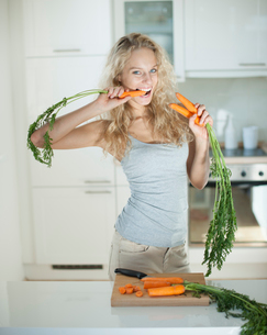 Woman eating carrot at kitchen counterの写真素材 [FYI03652184]