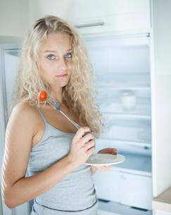 Portrait of sad woman having cherry tomato in kitchenの写真素材 [FYI03652194]