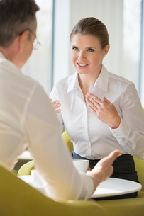 Businesswomen explaining to male colleague at office lobbyの写真素材 [FYI03652230]