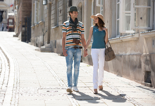 Tourist couple holding hands while walking on sidewalkの写真素材 [FYI03652266]