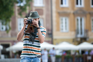 Young man photographing through vintage camera outdoorsの写真素材 [FYI03652267]