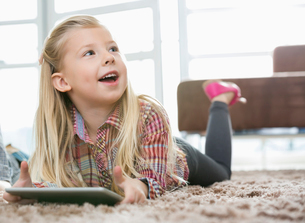 Cute girl with digital tablet looking away while lying on rug in living roomの写真素材 [FYI03652311]