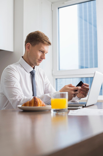 Mid adult businessman using cell phone with laptop on breakfast tableの写真素材 [FYI03652337]