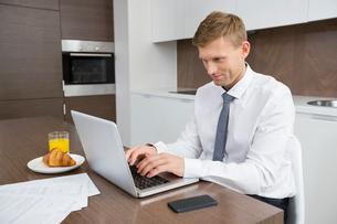 Businessman using laptop at breakfast tableの写真素材 [FYI03652339]